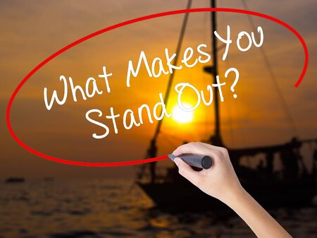 differentiation: Woman Hand Writing What Makes You Stand Out? with a marker over transparent board. Isolated on Sunset Boat. Business concept. Stock Photo