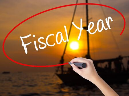 fiscal: Woman Hand Writing Fiscal Year with a marker over transparent board. Isolated on Sunset Boat. Business concept. Stock Photo