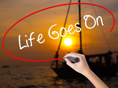 Woman Hand Writing Life Goes On with a marker over transparent board. Isolated on Sunset Boat. Business concept. Stock Photo Stock Photo