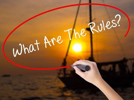 Woman Hand Writing What Are The Rules?  with a marker over transparent board. Isolated on Sunset Boat. Business concept. Stock Photo Stock Photo