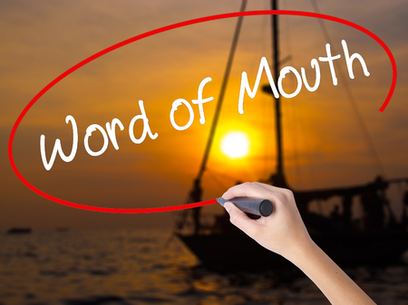 referrer: Woman Hand Writing Word of Mouth  with a marker over transparent board. Isolated on Sunset Boat. Business concept. Stock Photo