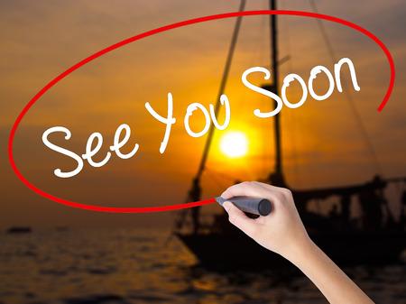 will return: Woman Hand Writing See You Soon with a marker over transparent board. Isolated on Sunset Boat. Business concept. Stock Photo Stock Photo