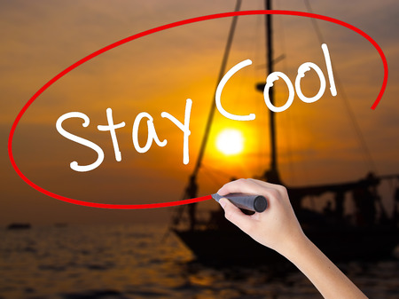 Woman Hand Writing Stay Cool   with a marker over transparent board. Isolated on Sunset Boat. Business concept. Stock Photo