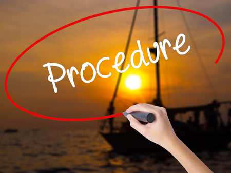 sop: Woman Hand Writing Procedure with a marker over transparent board. Isolated on Sunset Boat. Business, technology, internet concept. Stock Photo
