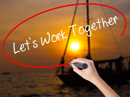 combined effort: Woman Hand Writing Lets Work Together with a marker over transparent board. Isolated on Sunset Boat. Business concept. Stock Photo