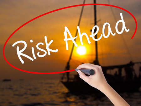 Woman Hand Writing Risk Ahead with a marker over transparent board. Isolated on Sunset Boat. Business, technology, internet concept. Stock Image
