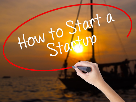 sucessful: Woman Hand Writing How to Start a Startup with a marker over transparent board. Isolated on Sunset Boat. Business concept. Stock Photo Stock Photo