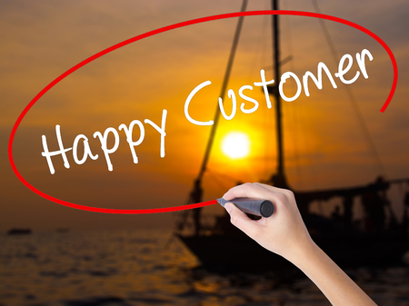 Woman Hand Writing Happy Customer with a marker over transparent board. Isolated on Sunset Boat. Business concept. Stock Photo