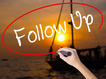 objections: Woman Hand Writing Follow Up with a marker over transparent board. Isolated on Sunset Boat. Business concept. Stock Photo