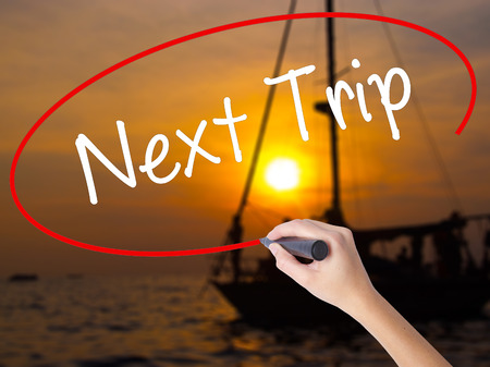 trip over: Woman Hand Writing Next Trip with a marker over transparent board. Isolated on Sunset Boat. Business concept. Stock Photo