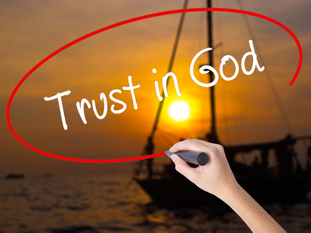 Woman Hand Writing Trust in God with a marker over transparent board. Isolated on Sunset Boat. Business concept. Stock Photo