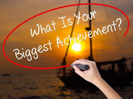 overachieving: Woman Hand Writing What Is Your Biggest Achievement? with a marker over transparent board. Isolated on Sunset Boat. Business concept. Stock Photo Stock Photo