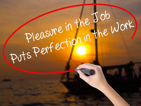 perfectionist: Woman Hand Writing Pleasure in the Job Puts Perfection in the Work with a marker over transparent board. Isolated on Sunset Boat. Business concept. Stock Photo