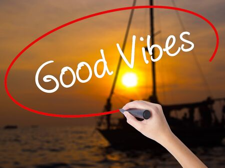 positivismo: Woman Hand Writing Good Vibes with a marker over transparent board. Isolated on Sunset Boat. Business concept. Stock Photo
