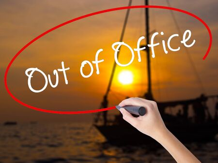 Woman Hand Writing Out of Office with a marker over transparent board. Isolated on Sunset Boat. Business concept. Stock Photo
