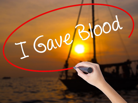 generosa: Woman Hand Writing I Gave Blood with a marker over transparent board. Isolated on Sunset Boat. Business concept. Stock Photo