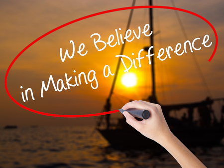 Woman Hand Writing We Believe in Making a Difference with a marker over transparent board. Isolated on Sunset Boat. Business concept. Stock Photo Stock Photo