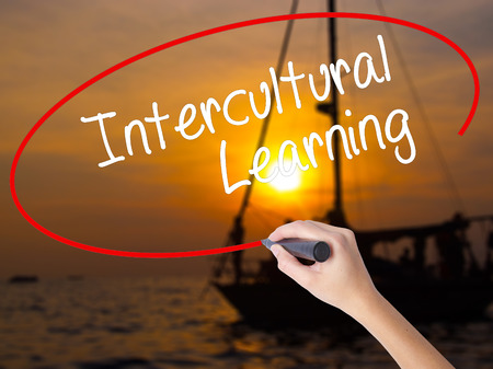intercultural: Woman Hand Writing Intercultural Learning with a marker over transparent board. Isolated on Sunset Boat. Business concept. Stock Photo