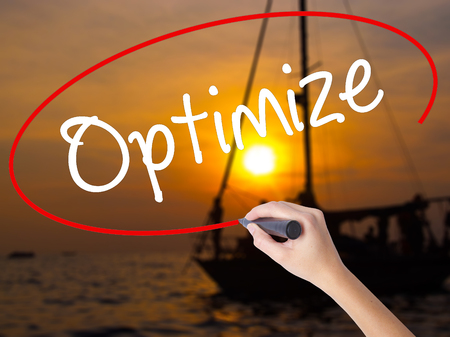Woman Hand Writing Optimize with a marker over transparent board. Isolated on Sunset Boat. Business concept. Stock Photo Stock Photo