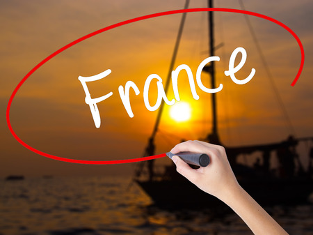 Woman Hand Writing France with a marker over transparent board. Isolated on Sunset Boat. Business concept. Stock Photo