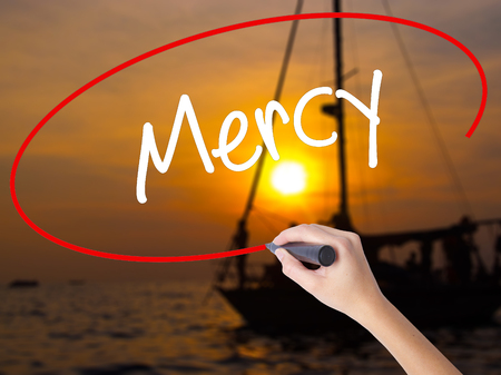 absolution: Woman Hand Writing Mercy with a marker over transparent board. Isolated on Sunset Boat. Business concept. Stock Photo Stock Photo