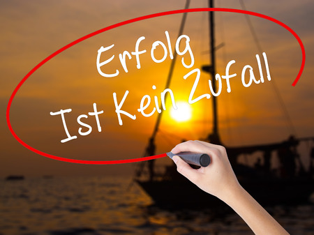 boat accident: Woman Hand Writing Erfolg Ist Kein Zaufall (Success Is No Accident in German) with a marker over transparent board. Isolated on Sunset Boat. Business concept. Stock Photo Stock Photo
