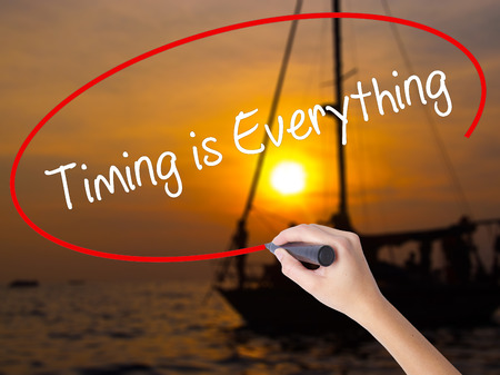 rigor: Woman Hand Writing Timing is Everything with a marker over transparent board. Isolated on Sunset Boat. Business concept. Stock Photo