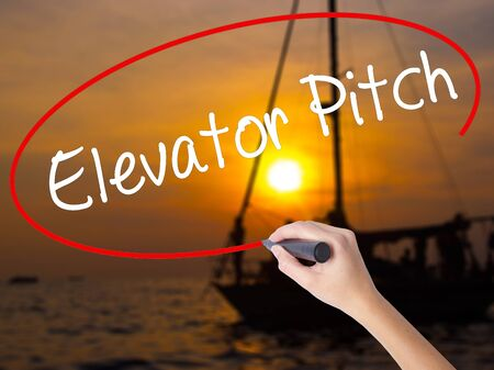 business pitch: Woman Hand Writing Elevator Pitch with a marker over transparent board. Isolated on Sunset Boat. Business concept. Stock Photo