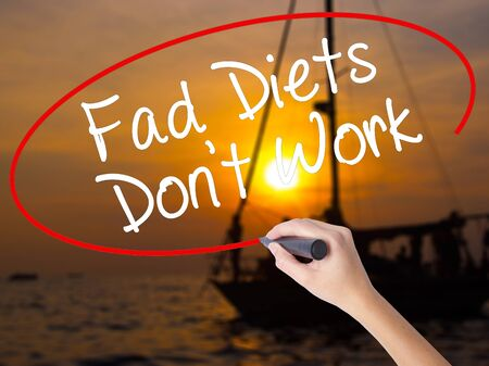 work boat: Woman Hand Writing Fad Diets Dont Work with a marker over transparent board. Isolated on Sunset Boat. Business concept. Stock Photo Stock Photo