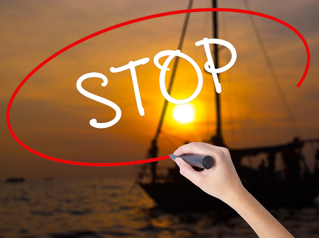 layoffs: Woman Hand Writing STOP  with a marker over transparent board. Isolated on Sunset Boat. Business concept. Stock Photo