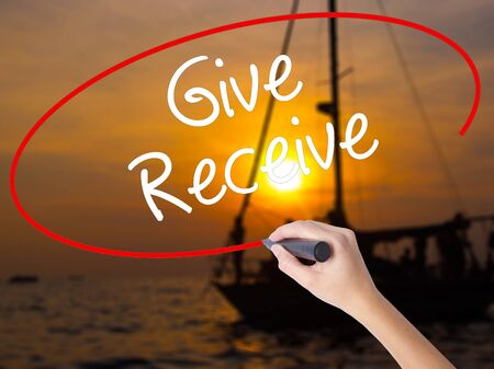 Woman Hand Writing Give Receive with a marker over transparent board. Isolated on Sunset Boat. Business concept. Stock Photo