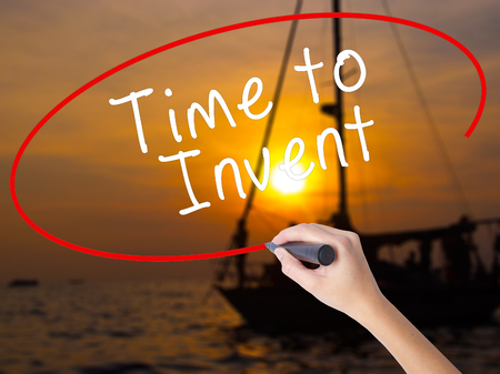 invent: Woman Hand Writing Time to Invent with a marker over transparent board. Isolated on Sunset Boat. Business, technology, internet concept. Stock Image