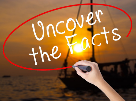 actuality: Woman Hand Writing Uncover the Facts with a marker over transparent board. Isolated on Sunset Boat. Business, technology, internet concept. Stock Image Stock Photo