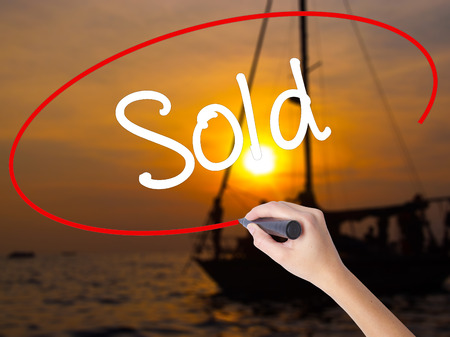 Woman Hand Writing Sold with a marker over transparent board. Isolated on Sunset Boat. Business concept. Stock Photo Stock Photo