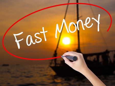 earn google: Woman Hand Writing Fast Money  with a marker over transparent board. Isolated on Sunset Boat. Business concept. Stock Photo