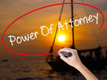 Woman Hand Writing Power Of Attorney with a marker over transparent board. Isolated on Sunset Boat. Business concept. Stock Photo