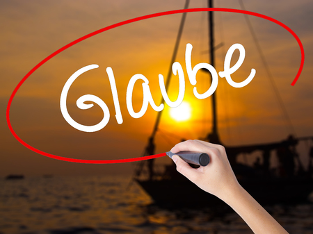 glaube: Woman Hand Writing Glaube (Believe in German) with a marker over transparent board. Isolated on Sunset Boat. Business concept. Stock Photo Stock Photo