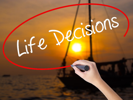 Woman Hand Writing Life Decisions with a marker over transparent board. Isolated on Sunset Boat. Business concept. Stock Photo