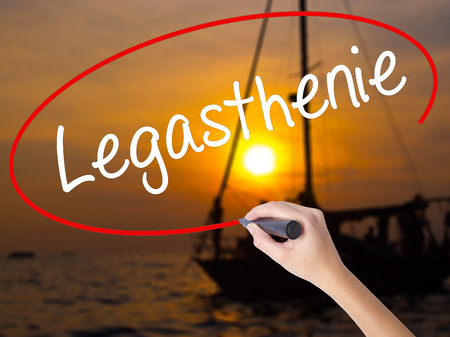 reversing: Woman Hand Writing Legasthenie (Dyslexia in German) with a marker over transparent board. Isolated on Sunset Boat. Business concept. Stock Photo Stock Photo