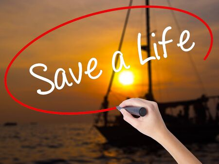 t bar: Woman Hand Writing Save a Life  with a marker over transparent board. Isolated on Sunset Boat. Business concept. Stock Photo