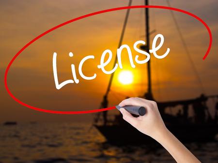 Vrouw Hand schrijven licentie met een marker over transparant bestuur. Geïsoleerd op Sunset Boat. Bedrijfsconcept. Stock foto