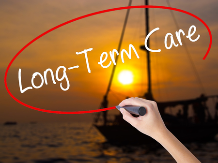 ltc: Woman Hand Writing Long-Term Care with a marker over transparent board. Isolated on Sunset Boat. Business concept. Stock Photo