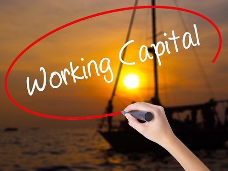 Woman Hand Writing Working Capital with a marker over transparent board. Isolated on Sunset Boat. Business concept. Stock Photo