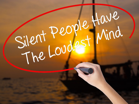 Woman Hand Writing Silent People Have The Loudest Mind with a marker over transparent board. Isolated on Sunset Boat. Business concept. Stock Photo