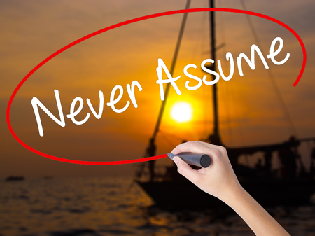inferring: Woman Hand Writing Never Assume with a marker over transparent board. Isolated on Sunset Boat. Business concept. Stock Photo Stock Photo