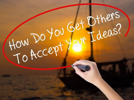 Woman Hand Writing How Do You Get Others To Accept Your Ideas? with a marker over transparent board. Isolated on Sunset Boat. Business concept. Stock Photo Stock Photo