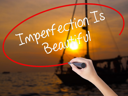 perfectionist: Woman Hand Writing Imperfection Is Beautiful with a marker over transparent board. Isolated on Sunset Boat. Business concept. Stock Photo