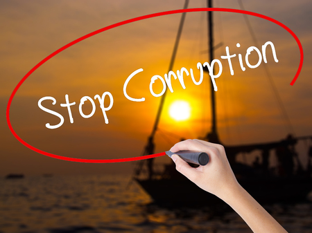 misconduct: Woman Hand Writing Stop Corruption with a marker over transparent board. Isolated on Sunset Boat. Business concept. Stock Photo