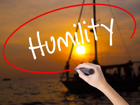 humility: Woman Hand Writing Humility  with a marker over transparent board. Isolated on Sunset Boat. Business concept. Stock Photo