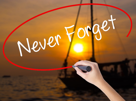 Woman Hand Writing Never Forget  with a marker over transparent board. Isolated on Sunset Boat. Business concept. Stock Photo